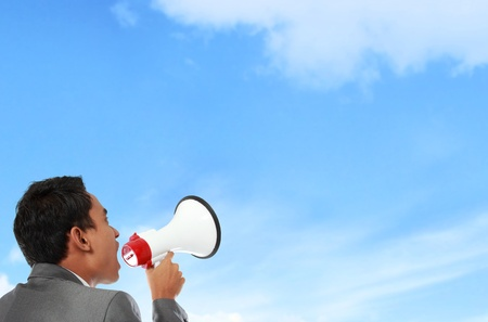 loudspeaker: business man shouting using megaphone under the blue sky