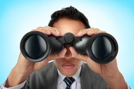 Primer plano de un joven hombre de negocios mirando a través de binoculares Foto de archivo