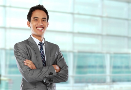 Happy young business man looking at camera with satisfaction at office photo
