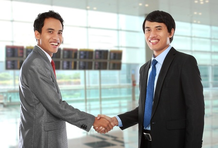 business colleagues shaking hands and smiling to the camera photo