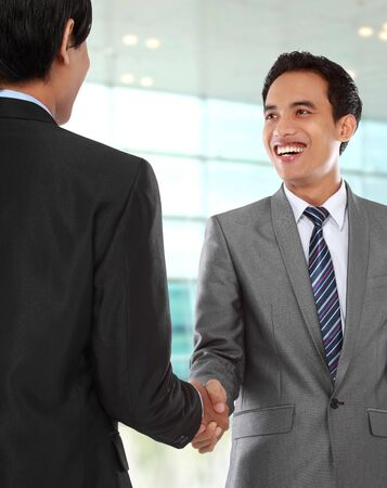 attractive business colleagues shaking hands and smiling photo