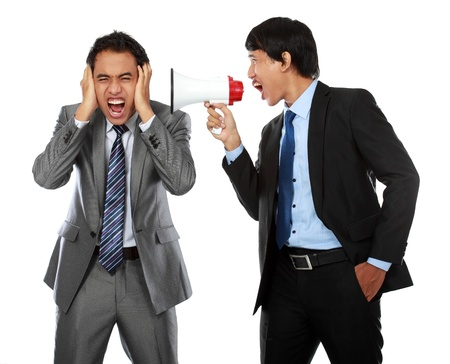 boss shouting over his employees ear, using megaphone isolated over white background photo