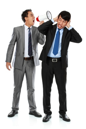 bellowing: boss shouting over his employees ear, using megaphone isolated over white background Stock Photo