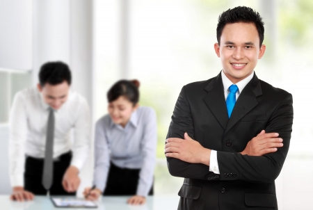 Happy young business man looking at camera with satisfaction at office Stock Photo - 14373739