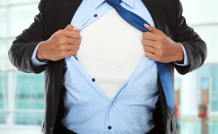 Businessman showing a superhero suit underneath his suit in the office photo