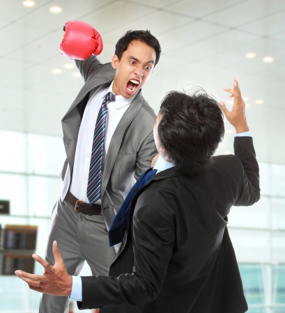 businessman hit his rival in the face at the office photo