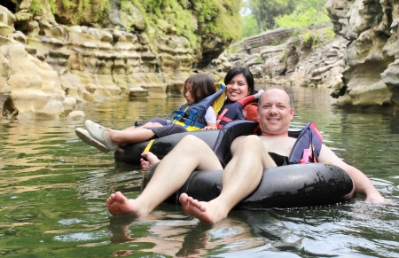float tube: Happy family floating on inflatable tube in river during vacation Stock Photo