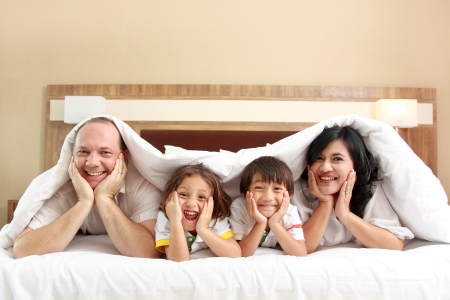Happy family looking at the camera on their bed photo