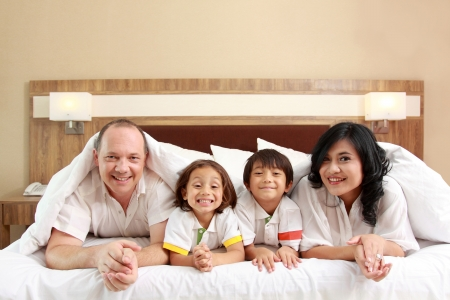 happy family on white bed in the bedroom photo