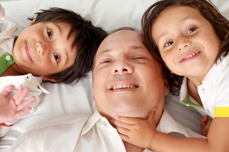 Closeup portrait of a happy father and son together in the bedroom photo