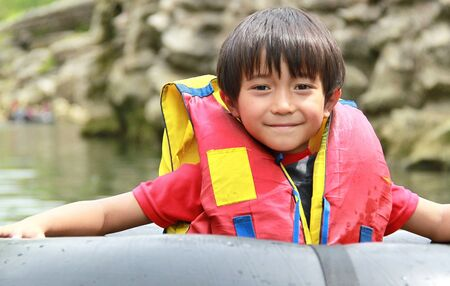 Happy kid floating on inflatable tube in river during vacation photo