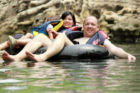 Happy family floating on inflatable tube in river during vacation photo