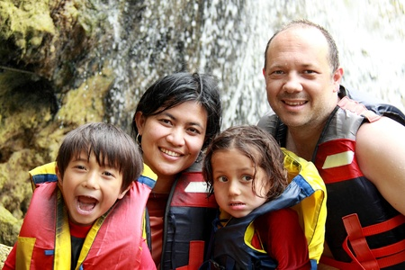 Cheerful family wearing life vest smiling at camera photo