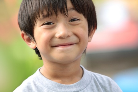 close up image: close up portrait of cute boy smiling in the park