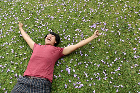 happy man lying on the grass with arm raised photo
