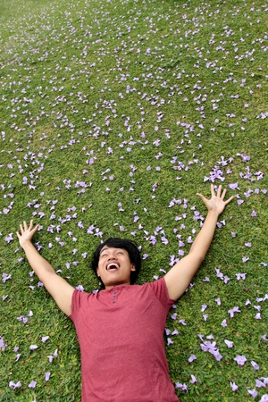 happy asian man lying on the grass photo