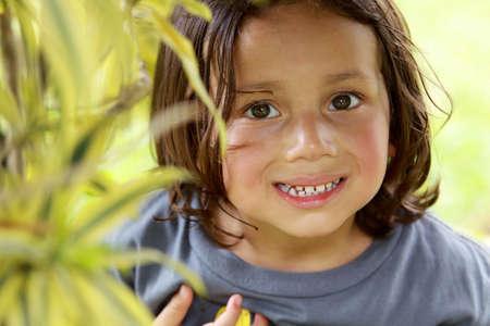 Portrait of happy cute little boy smiling in the park photo