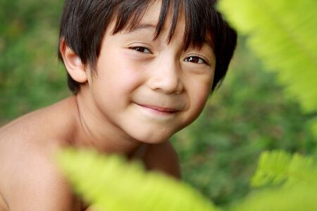 Portrait of happy joyful little boy playing in the park photo