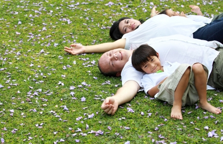 happy Family lying down in the park Stock Photo