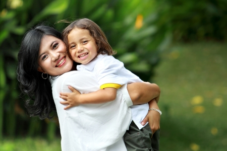 Cute cheerful child with mother play outdoors photo