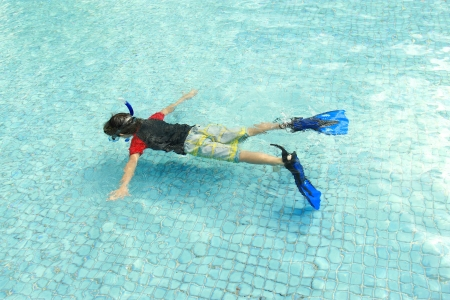 snorkling: kid swimming in the pool using snorkling equipment