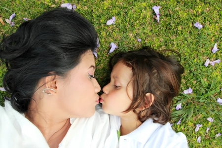 mom kiss son: Cute cheerful child with mother play outdoors in the park