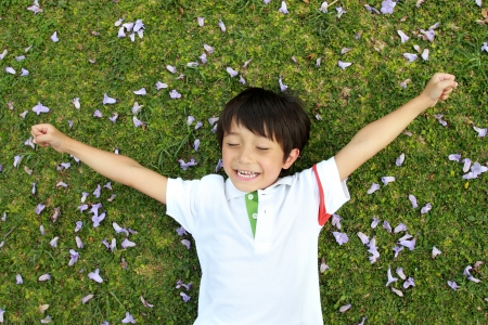 cheerful boy laying on the green grass photo