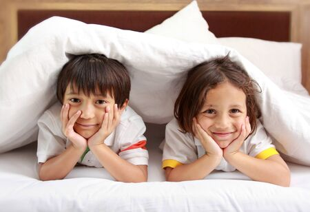 Two little boy smiling relaxing in the bedroom photo