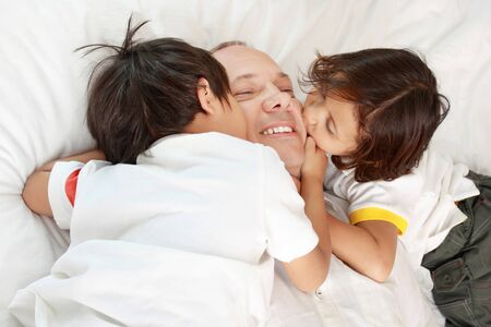 son kissing their father on the bed photo