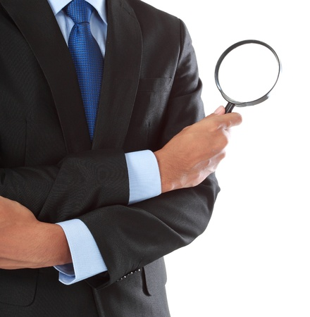 magnifying glass: business man holding magnifying glass isolated on white background