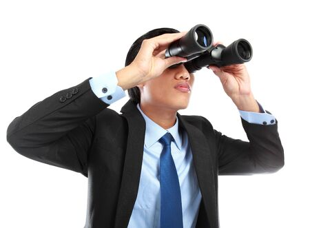 Closeup of a young business man looking through binocular isolated on white background photo