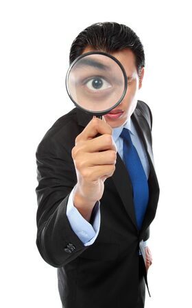 business concept - businessman looking through magnifying glass photo