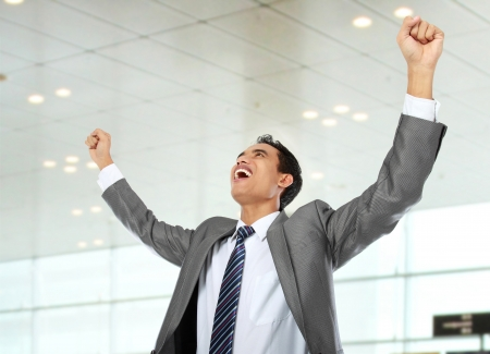 Excited business man celebrating success in the office photo