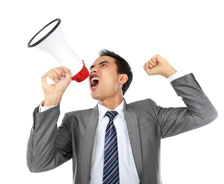 bellowing: close up portrait of young man shouting using megaphone isolated on white background