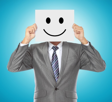 businessman covering his face with smiling mask on blue background Stock Photo