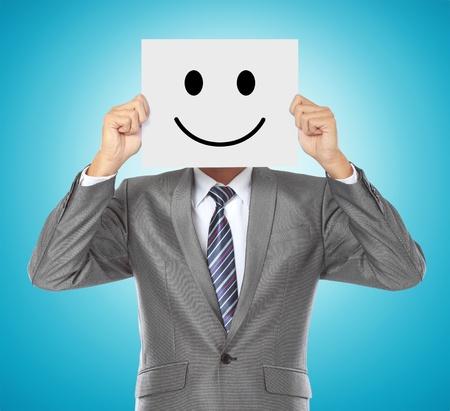 zakenman die zijn gezicht met lachende masker op blauwe achtergrond