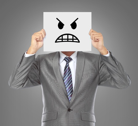 businessman covering his face with angry mask on gray background