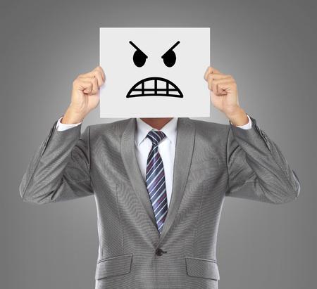 hombre de negocios que cubre su rostro con la máscara de ira sobre fondo gris
