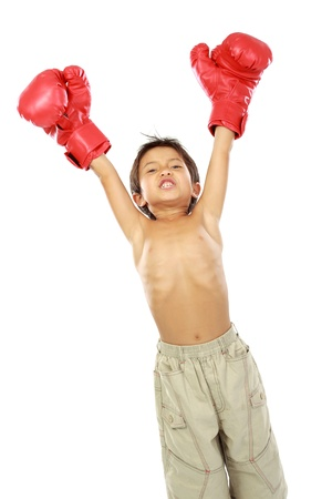 portrait of happy young boy with boxing glove. winning pose photo