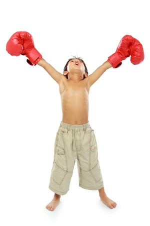 winning race: portrait of happy young boy with boxing glove. winning pose