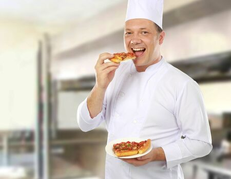 chef eating and taste a pizza of his in the kitchen photo