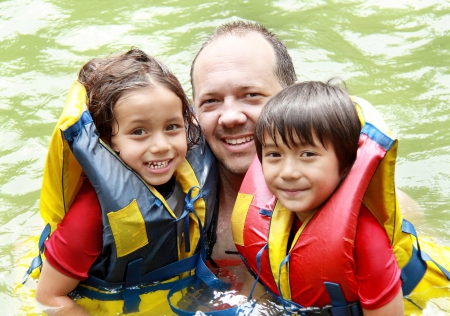 outbound: Cheerful family in the water wearing life vest smiling at camera Stock Photo