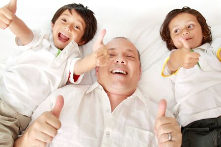 endearment: the father and son laying on the bed showing thumb up Stock Photo