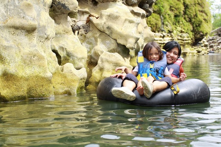 float tube: Happy mother and son floating on inflatable tube in river during vacation Stock Photo