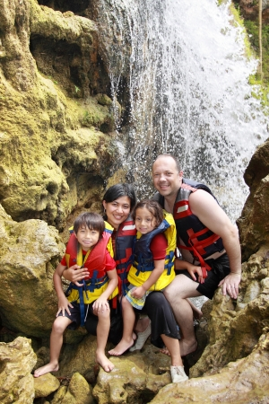 outbound: Cheerful family in waterfall area wearing life vest smiling at camera Stock Photo