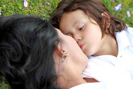 mom kiss son: Cute little boy and her mother kissing in the park Stock Photo