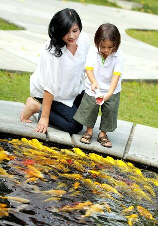 children pond: mother and son feeding the fish in the park