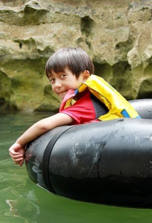 outbound: Happy kid floating on inflatable tube in river during holiday vacation