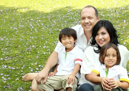 family holidays: Portrait of happy asian caucasian family in the park Stock Photo