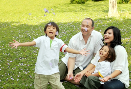 active holiday: Portrait of happy asian caucasian family in the park Stock Photo